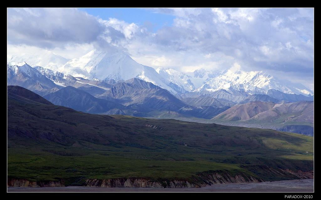 Аляска. Вид на гору Мак-Кинли из Национального парка Денали. Мак-Кинли - высочайшая гора Северной Америки (6194 м). Kогда Аляска еще принадлежала России эту гору называли Великая (в переводе с языка атабасков). Потом уже переименовали в честь 25-го президента США. По сложности восхождения Мак-Кинли равна самой высокой горе мира Эвересту.Alaska Mount McKinley Тундра Гряды Аляскинского хребта Мак-Кинли Снег Облака PARADOX