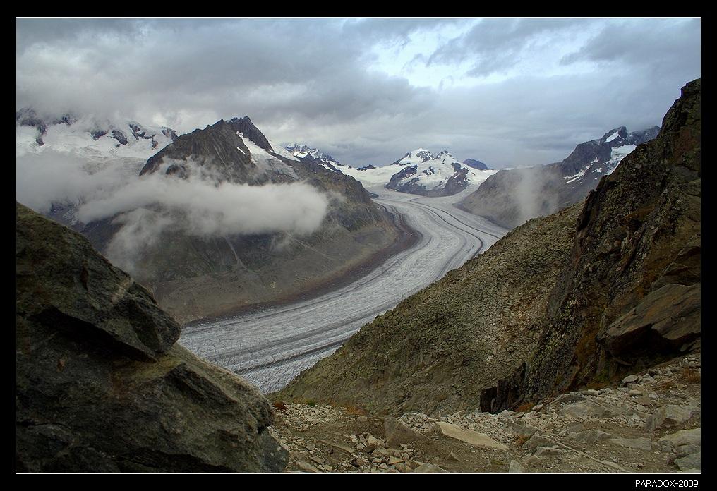 *  *  *Горы начинают затягиваться гусеницами облаков, чтобы вскоре скрыться в тумане ... Каменный профиль внизу слева задумчиво взирает на обрывистый спуск в долину ... А сам ледник образовал рукава, очень похожие на дороги ...*  *  *Алечский ледник – крупнейший в Альпах, 27 биллионов тонн льда толщиной до 790 м.Вид с высоты 2926 м, северного склона горы Эгисхорн.