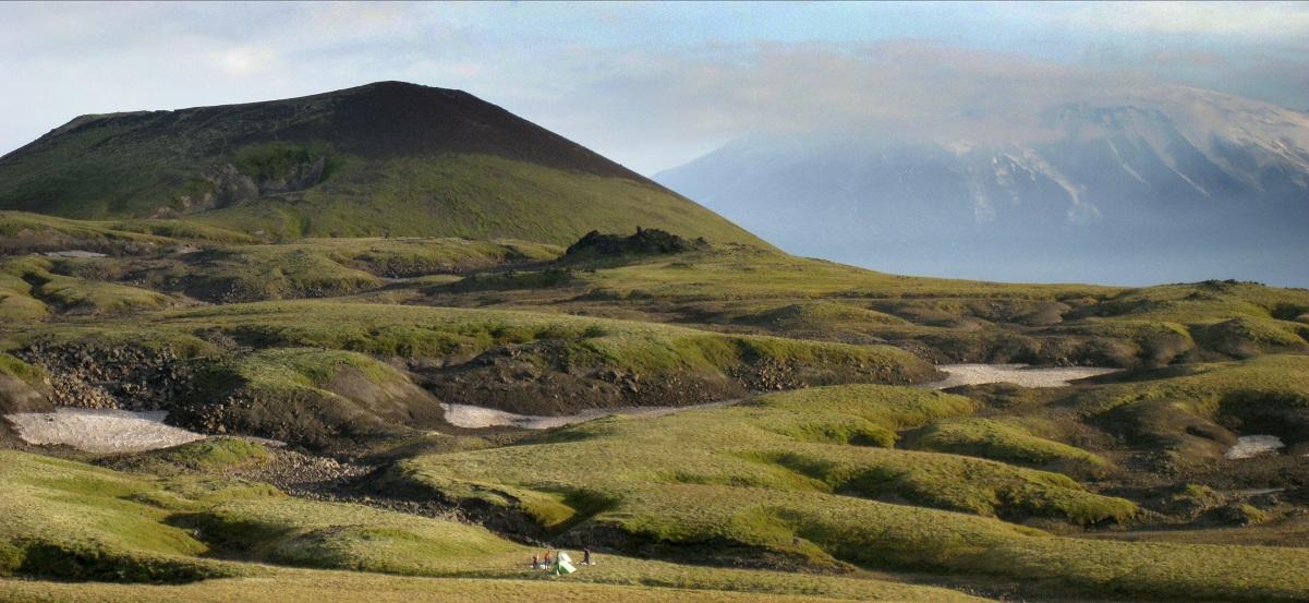 Весьма типичный для Камчатки пейзаж, неяркая зелень, курумник... Но впереди - горы, которые ждут нас.Наша палатка - маленькое пятнышко на этом просторном  плато. Кстати, в этот момент к нам близко подошли два медведя, поэтому группа очень обеспокоена моим отсутствием