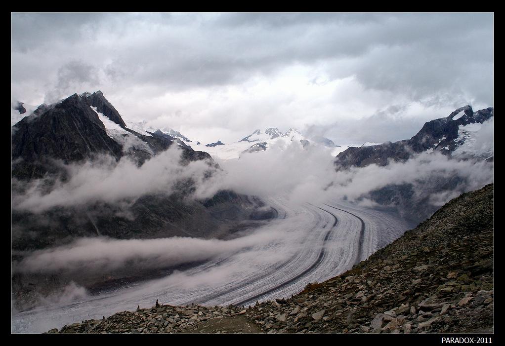 *  *  *  Еще несколько минут назад ничто не предвещало непогоды. Но внезапно небо насупилось, густой туман начал запускать змеи облаков на понравившиеся ему участки ... А вскоре и весь вид на ледник и горы покроется сплошной пеленой тумана ...*  *  * Бернские Альпы, Швейцария. Большой Алечский ледник, вид с высоты 2926 м, со склона горы Эггисхорн.