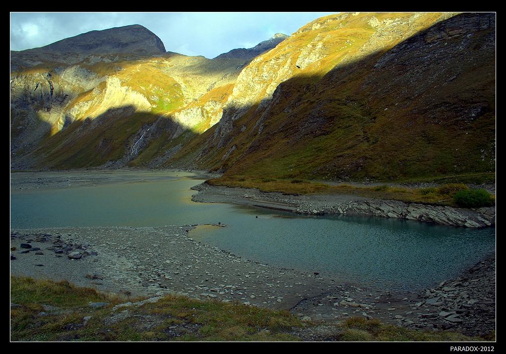 *  *  *Солнечная птица, раскрывшая свои крылья на склонах горных исполинов, уже не достает до озерной глади. А еще через несколько мгновений тенистое покрывало поглотит ее полностью ...*  *  *Австрия, Высокогорная альпийская дорога Гроссглокнер.