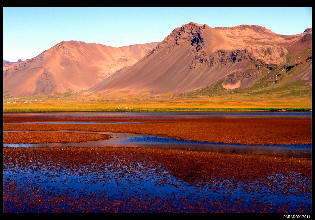 """*  *  *Раудaсандур (""""Красные пески""""), расположенный в отдаленном районе острова, называют самым хорошо охраняемым секретом Исландии. Добраться сюда нелегко - многочасовый путь по каменистой дороге вдоль крутых обрывов. Возможно, названием это место обязано удививителным краскам песчаных отмелей в фиорде и розовым оттенкам прилегающих гор ...*  *  *Исландия, Западные фиорды, Raudasandur"""