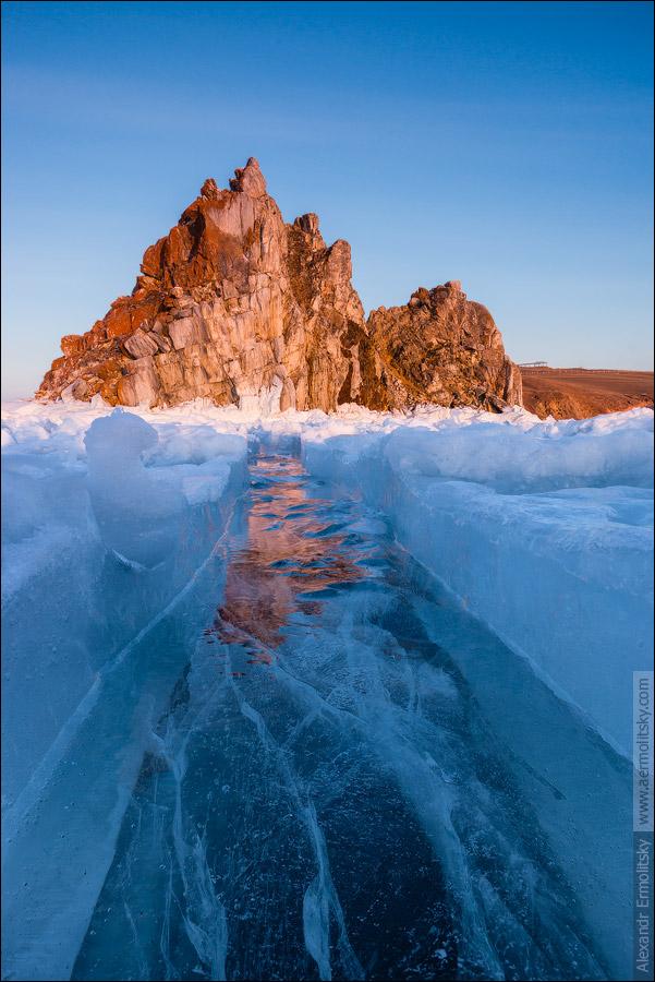 """Лёд Байкала постоянно меняется, трескается, """"дышит"""". Свежая трещина, от силы два дня от роду, уже успела замёрзнуть и потрескаться. К счастью, ветер ещё не забил её снегом, так что в молодом льде отражается скала Шаманка, подсвеченная последними лучами заходящего солнца. Россия, Иркутская область, озеро Байкал, остров Ольхон, мыс Бурхан (скала Шаманка), март 2014"""
