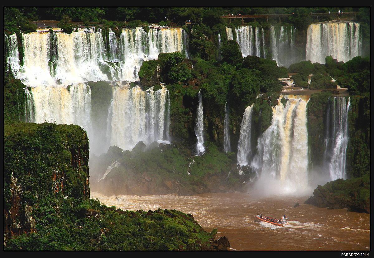*  *  *Лодка доставляет  пассажиров прямо  под поток водопада, остаться сухим  нет никаких шансов ... Фототехника прячется в специально выдаваемые герметичные кожаные мешки.*  *  *Водопады Игуасу, Бразилия.