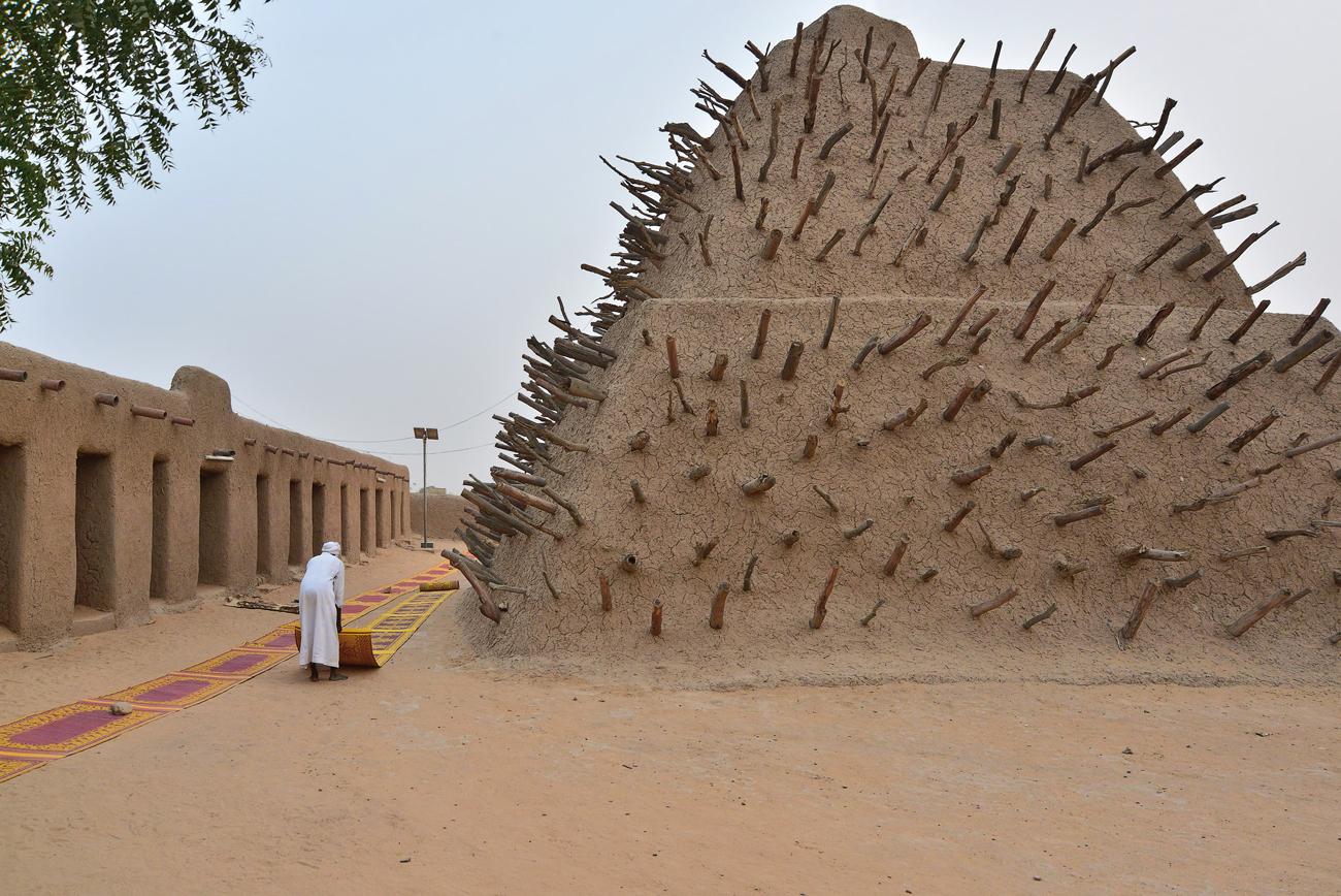 Эффектное 17-метровое пирамидальное сооружение-гробница было воздвигнуто в 1495 г. императором Мохамедом I Аския в столице Сонгаи. Этот памятник – свидетельство силы, власти и богатства империи, которая процветала в XV-XVI вв. благодаря контролю над транссахарской торговлей, в основном – солью и золотом. Это также прекрасный пример традиционной монументальной глинобитной постройки на западной окраине Сахары. Комплекс, включающий пирамидальную гробницу, две мечети с плоскими крышами, кладбище при мечети, а также площадь под открытым небом для собраний, был построен, когда столицей империи Сонга