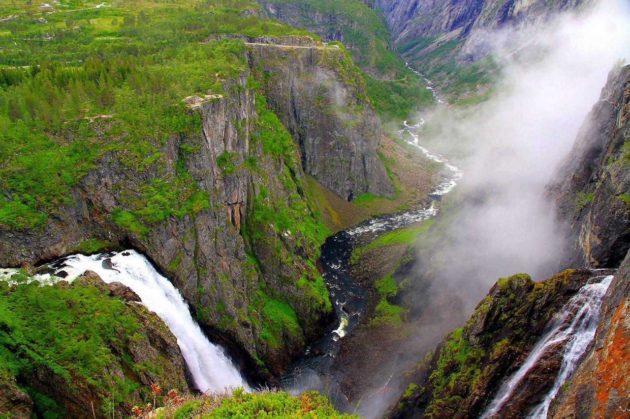 * * *Чтобы взглянуть на этот один из самых знаменитых водопадов Норвегии с верхней точки у обрыва, надо проехать по старой дороге, делающей 125 крутых поворотов.Да и рукава водопада петляют по крутым скальным склонам на фоне клубящихся туманов над ушельями горного массива Мобедален.* * *Водопад Вёрингсфоссен и долина Мобедален, провинция Хордаланд, Западная Норвегия