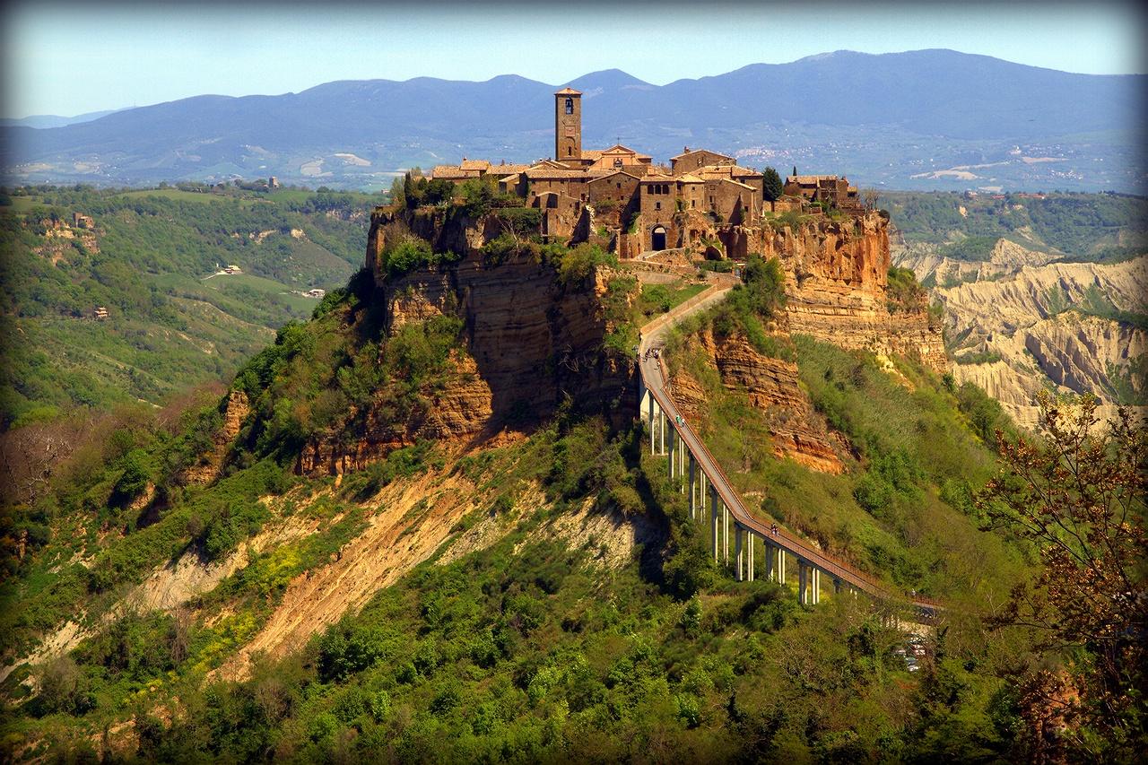 """* Основанный более 2500 лет назад, этот город подвергся ужасному землетрясению в 1695 г., за которым последовали новые. Жители покинули город, сегодня там живет 15 человек зимой и ок. 100 летом. В этом месте, получившем название """"Мертвый город"""", остановилось время. Считается одним из самых красивых средневековых городов Италии. Добраться до города-призрака можно только по крутому пешеходному мосту. *Civita di Bagnoregio, Италия, регион Лацио"""