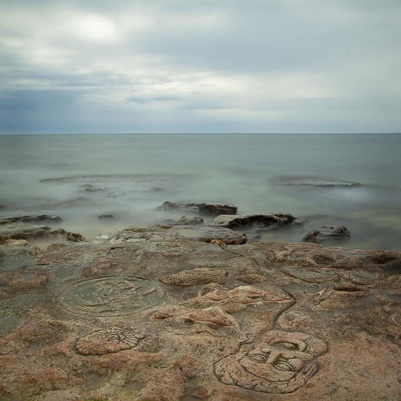 Крым. Мыс Херсонес. Пустынный берег, на котором художники-камнерезы создают новую достопримечательность. Ежегодно на камнях появляются новые барельефные изображения фантастических животных и рыб.