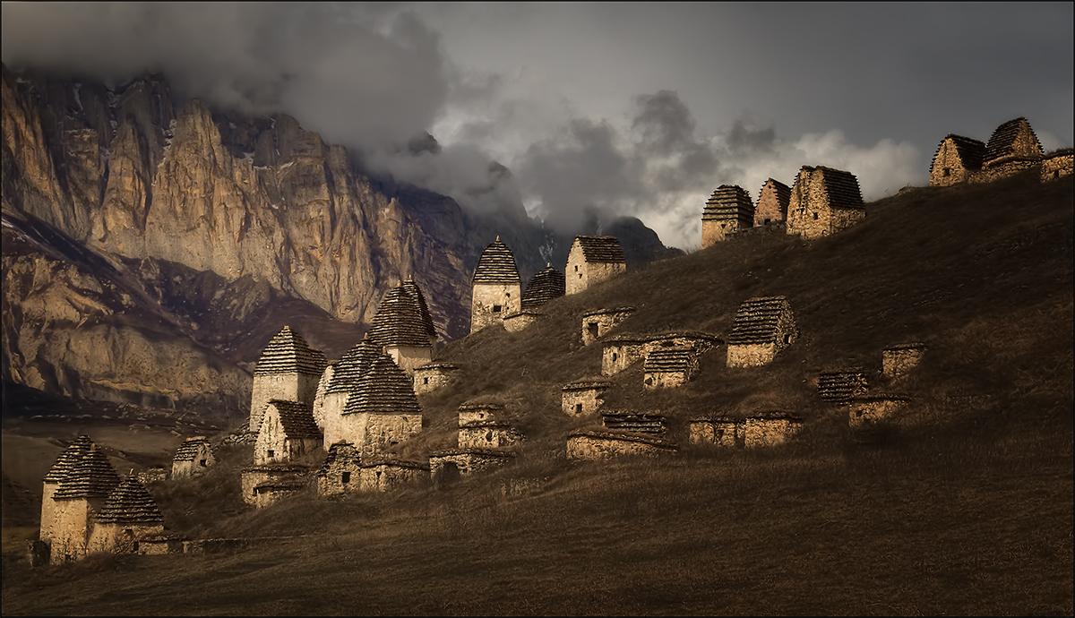 Город мертвых Даргавс в переводе с осетинского означает «защитник ущелья». Это удивительный архитектурный комплекс, расположенный в одноименном селе Пригородного района Северной Осетии – Алании, в самом центре горной долины, раскинувшейся на 17 км. Город мертвых Даргавс – крупнейший на Северном Кавказе склеповый могильник, представляющий собой комплекс из более чем 90 фамильных усыпальниц.