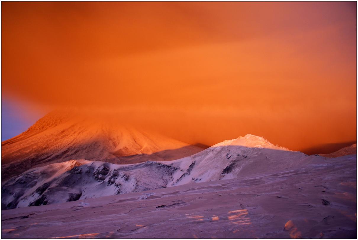 Вулкан выбросил в атмосферу тысячи тонн пепла. Пепельная туча, подсвеченная зимним солнцем, пламенем охватила окружающий мир. Все  замерли в страхе перед стихией. Февраль 2011. Цвета реальные.