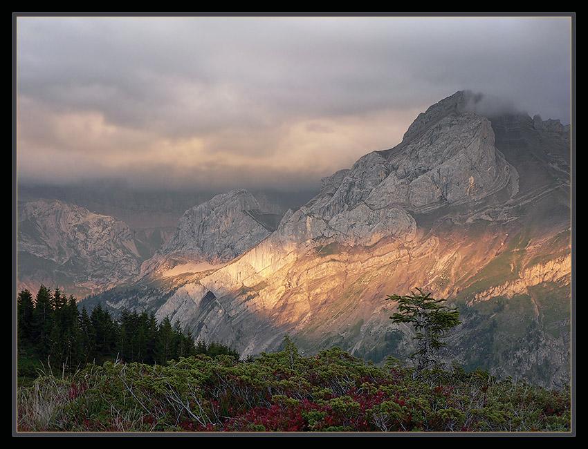 Вечер. На один момент луч заходящего солнца пробился сквозь сгущавшиеся тучи, и осветил горный массив ярким светом.