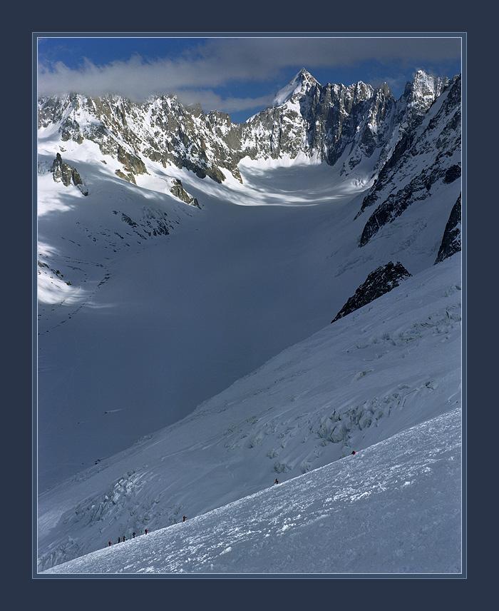 Спуск группы лыжников-альпинистов с Grand-Montets, Франция. На заднем плане доминирует гора Mont Dolent, на вершине которой встречаются границы Франции, Италии и Швейцарии.