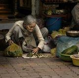 Старушка закончила торговлю принесенными овощами и старается убраться после себя, чтобы завтра не прогнали с насиженного места. Натруженные руки говорят сами за себя лучше любой трудовой книжки.