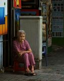 Уставшая дышать запахом красок в тесной и плохо освещенной мастерской, МАСТЕР - старушка вышла вдохнуть свежего воздуха, сделать пару глотков чаю со льдом, дать отдохнуть глазам и просто поглазеть на прохожих.