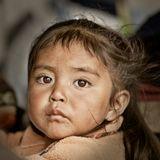 Эквадор.Маленькая девочка вместе с мамой ранним утромна рынке помогает продавать ей вещи,сделанные в подсобном хозяйстве:сумки, одежду, нехитрые сувениры.