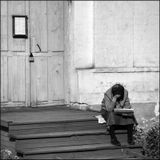 Женщина ждет вечерней службы на крылечке церкви