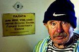 """одна из бесплатных Киевских больниц, этого дедушку я увидел идущего по коридору и обратил внимание, что он заходит в палату №5 """"ПАЛАТА для ИОВ, УОВ, кавалеров Ордена Славы, Героев Советского Союза"""" я спросил дедушку - Как здоровье? Он остановился, и я сделал этот снимок. В палате стоит телевизор, единственный на всю больницу, который туда спонсировал какой-то депутат, будучи в больнице с визитом... В коридоре очень темно, я не хотел использовать вспышку, исо 1600 выдержка 1\5"""