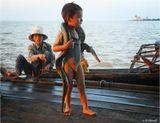 Камбоджа. Озеро Тонлесап. Здесь люди (главным образом мигранты-вьетнамцы) живут на воде - в домах на сваях. В озеро, кишащее рыбой, змеями и крокодилами, сбрасывают отходы, из него же пьют, тут же купаются. Занимаются либо выращиванием риса (за 5 долларов в день), либо побирательством среди туристов, демонстрируя им земноводных, как на снимке, или просто прося подачку в бакс-другой.