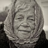 Эта женщина просит милостыню возле центрального собора нашего города. Когда на улице тепло, она сидит на ступеньках. Сейчас похолодало и она перешла на лавочку рядом с собором. По статистике ООН, за чертой бедности в Украине находятся 78% людей. По данные Росстата за чертой бедности находится 16% населения России.