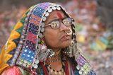 Индия.Женщины Раджастана носят не сари, а комплект из юбки, длинной приталенной рубахи и большого платка, напоминая своим видом цыганок, особенно из-за обилия тяжеловесных серебряных украшений. Тяжелые серебряные ножные браслеты, большие красные, желтые или оранжевые тюрбаны, покрывала, украшенные кусочками зеркал являются частью сложного кастового языка, но для большинства иностранцев они воплощение экзотики Индии.