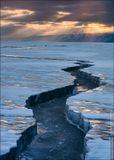 Замёрзшая трещина, разорвавшая лёд Байкала недалеко от мыса Трёх Братьев, и мягкий вечерний свет, пробивающийся через бреши в облаках.Россия, Иркутская область, озеро Байкал, март 2014