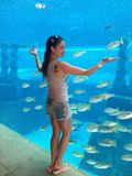 Девушка в сексапильных розовых тапочках в океанариуме.