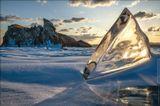 Первые лучи солнца преломляются в замёрзшем акульем плавнике около южной оконечности острова Огой.Россия, Иркутская область, озеро Байкал, март 2014
