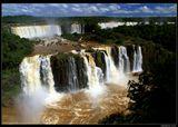 * * *  Симфония воды образована здесь 275 водопадами, расположенными на границе Бразилии и Аргентины. По результатам всемирного конкурса этот комплекс водопадов был признан одним из 7 природных чудес света.  * * *  Водопады Игуасу, вид из Бразилии (штат Парана)