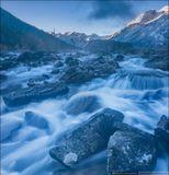 Шумы - это каменный завал, разделяющий Среднемультинское и Нижнемультинское озера. По сложившейся традиции его называют водопадом, хотя таковым он не является. Своё название он получил из-за сильного шума, который производит текущая между камнями вода. Этим утром было очень холодно, вода у берега озера замёрзла, над водопадом стлался туманчик, создававший атмосферу таинственности и волшебства.Россия, Республика Алтай, Катунский хребет.