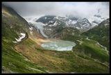 """Озеро """"Каменное"""" с высоты перевала Sustenpass как лужица. Непрозрачное, неглубокое, ледяное от талой воды, собранное из ручьев того скрытого облаками ледника на заднем плане. Усыпанное лугами весенних цветов в июне, отражающее грозовые тучи. Пики Альп тонут в  нескончаемых облаках, ветер сбивает с ног... И только когда косое вечернее солнце наконец подсветило склоны, чувствуешь, что и тут наступило  лето .... :)"""