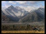 Отроги восточных Саян. Высота пиков более 2500 метров. У подножья уютно расположились деревушки.