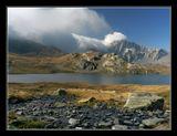 Lacs De Fenetre (2500m) Утро. С одной стороны озера нависли тучи, с другой желтую траву освещали лучи солнца.