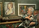 Художник в творческой мастерской, среди своих картин.